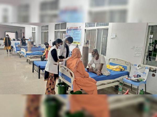 डेडिकेटेड कोविड सेंटर में मरीज को देखती एएनएम व चिकित्सक। - Dainik Bhaskar