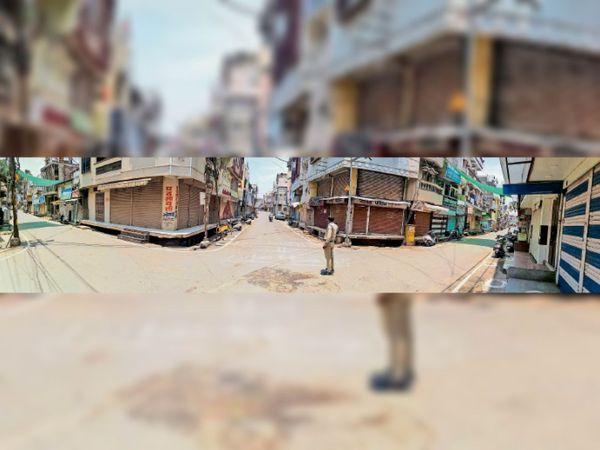 लाॅकडाउन के चलते बाजार में पसरे सन्नाटे के बीच आने-जाने वालाें काे टाेकता पुलिसकर्मी। - Dainik Bhaskar