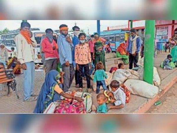 स्टैंड पर परिवार के साथ बस का इंतजार करते मजदूर। - Dainik Bhaskar