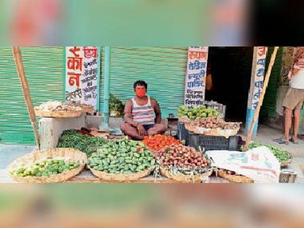 होटल बंद हो जाने के बाद फुटपाथ पर सब्जी बेचता संतोष राम। - Dainik Bhaskar
