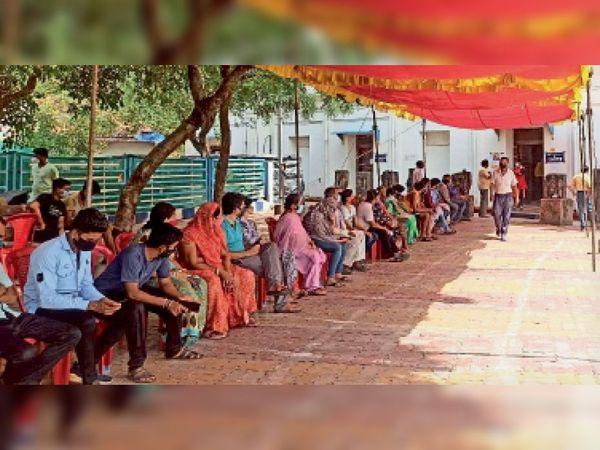 मल्हार स्मृति मंदिर में वैैक्सीनेशन के लिए अपनी बारी का इंतजार करते हुए कतार में बैठे लाेग। - Dainik Bhaskar