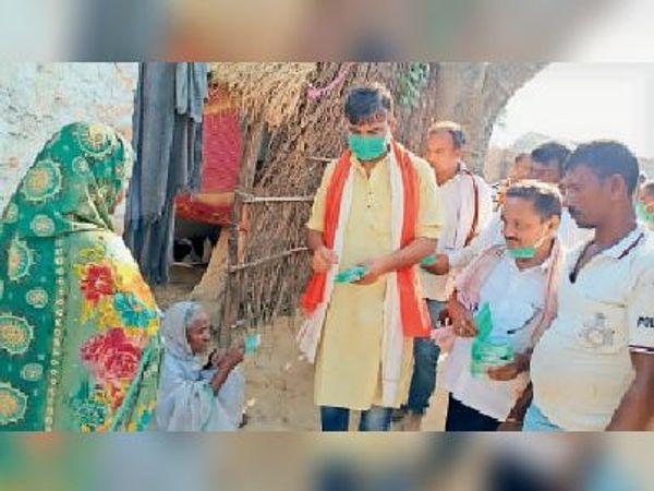 खड़गपुर नप क्षेत्र में ग्रामीणों को मास्क बांटते समाजसेवी ई. रोहित चौधरी। - Dainik Bhaskar
