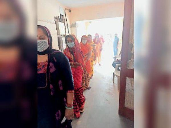 कोरोना वैक्सीन लगवाने के लिए सोशल डिस्टेंस में खड़ी महिलाएं। - Dainik Bhaskar