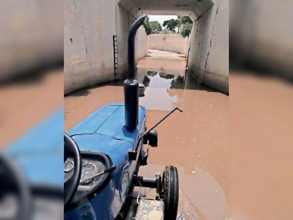 अंडर ग्राउंड पास में जमे पानी से निकलता ट्रैक्टर। - Dainik Bhaskar