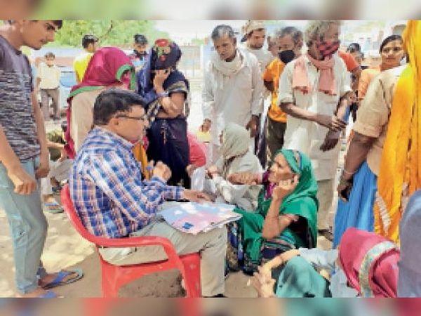 आकोदा के खुड़ाना में अधिकारी को अपने बयान लिखवाते हुए कुछ ग्रामीण। - Dainik Bhaskar