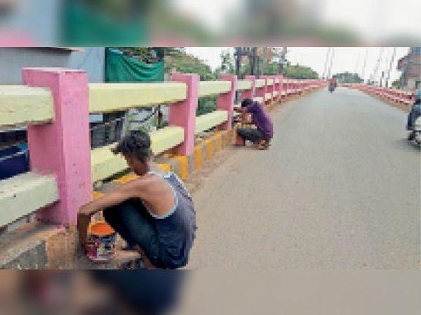 एफओबी की स्लैब पर पीले और काले रंग की पुताई करते कर्मचारी। - Dainik Bhaskar