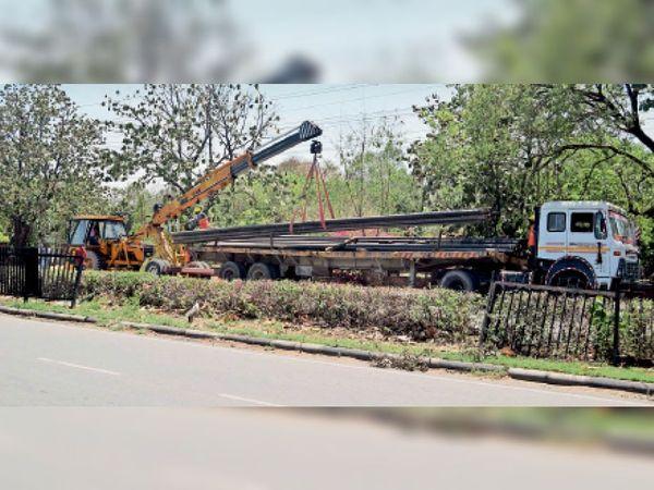 रविवार को इंडस्ट्रियल एरिया फेज-1 में गैस पाइपलाइन बिछाने के लिए एक बड़े ट्राले से पाइप उतारती क्रेन। - Dainik Bhaskar