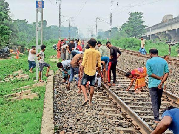 खगड़ा रेलवे फाटक के पास फेंके गए गांजे को उठाते लोग। - Dainik Bhaskar