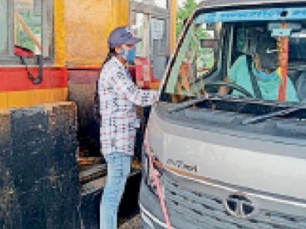 टोल पर वाहन चालक से समझाइश करती महिला स्टाफ। - Dainik Bhaskar