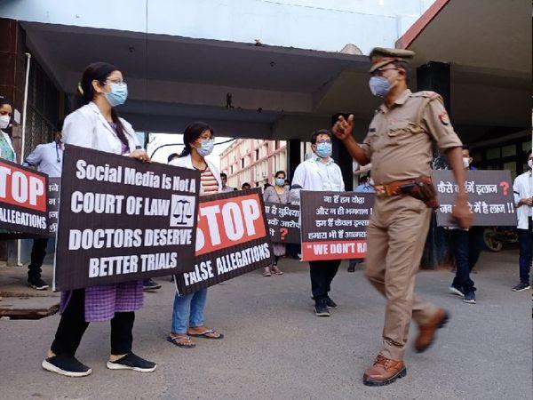 प्रदर्शन के दौरान डॉक्टरों को समझाता पुलिस अफसर।