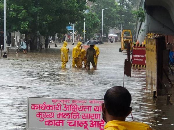 मुंबई के हिंदमाता इलाके में सड़क पर जमा पानी को हटाने का प्रयास करते BMC के कर्मचारी।