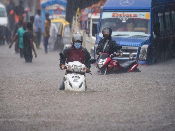 मुंबई के हिंदमाता इलाके में सड़क पर पानी भर जाने के कारण लोग गाड़ियों को खींचते हुए दिखे।