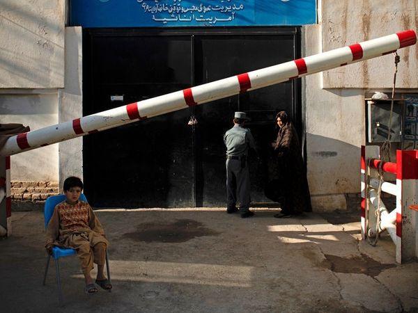 काबुल की एक जेल में जाती महिला गार्ड और बाहर बैठा बच्चा। (फाइल) - Dainik Bhaskar