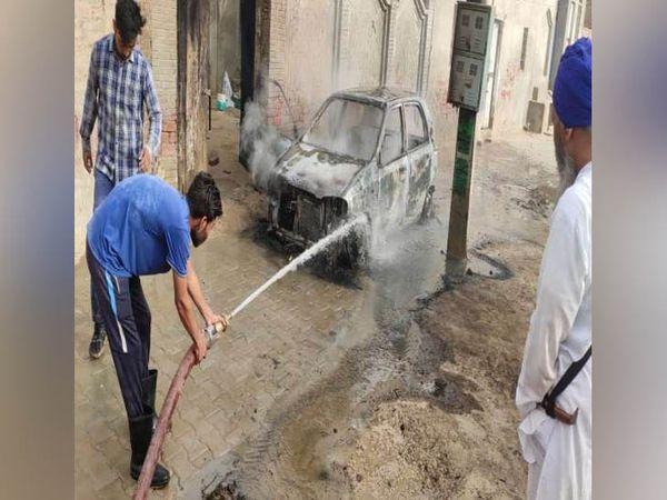 सिरसा जिले के कस्बा कालांवाली में कार में लगी आग को बुझाने के लिए पानी की बौछार डालते दमकल विभाग के कर्मचारी। - Dainik Bhaskar