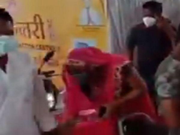 महिला ने मंत्री के पैर छूने की कोशिश की, मंत्री ने उन्हें आराम से वैक्सीन लगवाने को कहा।