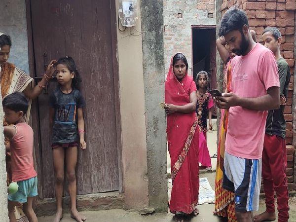मृत युवक के घर के बाहर मौजूद लोग। - Dainik Bhaskar