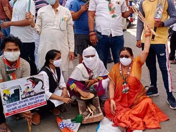 प्रदर्शन में महिला कार्यकर्ता चूल्हा, तवा भी साथ लाई। पेट्रोल पंप के बाहर की प्रतीकात्मक रूप से चूल्हे पर रोटी सेकी। - Dainik Bhaskar