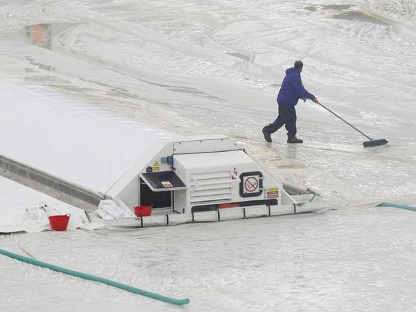 मैदान कर्मचारी मैदान से पानी हटाते हुए।