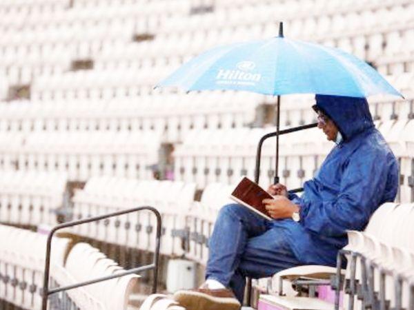 मैच के दौरान निराश दर्शक। बारिश के बीच छाते में वह किताब पढ़ता नजर आया।