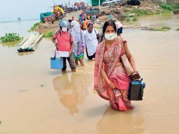 ये तस्वीर पटना के मोकामा की है। यहां सोमवार को डेढ़ फीट पानी पार कर घोसवारी प्रखंड के मोहनपुर गांव के मध्य विद्यालय में टीकाकरण के लिए टीम पहुंची।