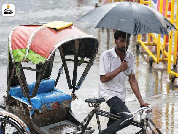 लखनऊ में बारिश के बीच छतरी तानकर जाता रिक्शा चालक।