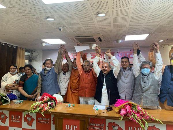 देहरादून में भाजपा विधायक दल की बैठक में पुष्कर सिंह धामी के नाम का ऐलान होने के बाद एकजुटता दिखाते हुए पार्टी नेता।