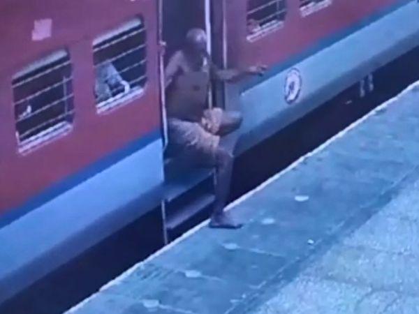 चलती ट्रेन से उतरने की कोशिश करता बुजुर्ग।