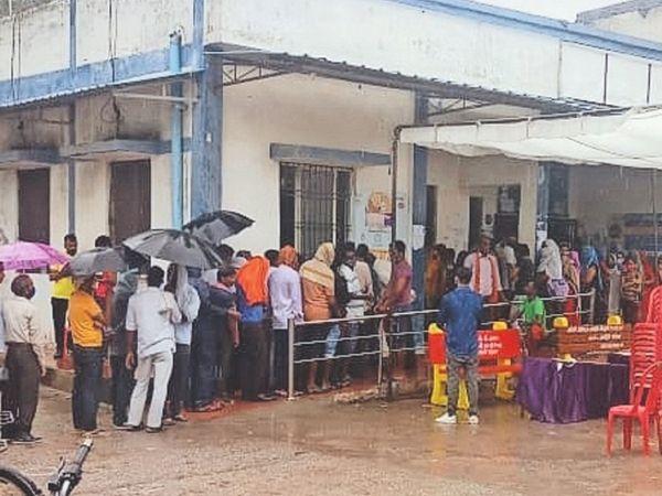 जिला अस्पताल मुरार में बारिश होने के बाद भी कोरोना से बचाव का टीका लगवाने के लिए लगी लोगों की लाइन। - Money Bhaskar