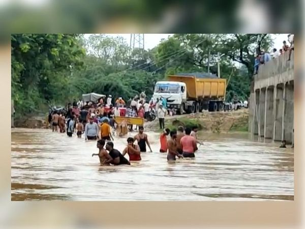 झिलमिल नदी के रपटा पुल पर आया पानी। निकलते हुए लोग। - Money Bhaskar