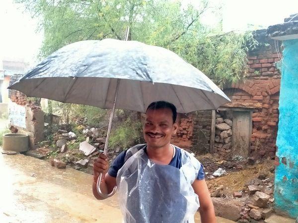 बारिश से बचाव करता युवक। - Money Bhaskar