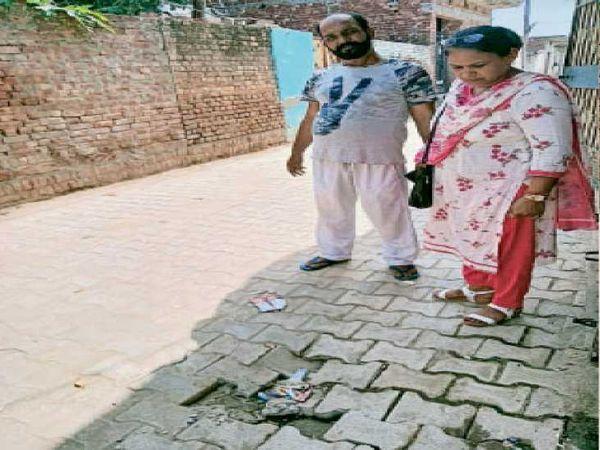 वार्ड 23 में उखड़ी टाइलें दिखातीं ट्रस्ट की सदस्य संतोष कुमारी। - Money Bhaskar