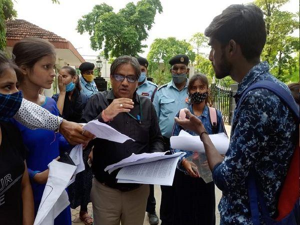 विवि के चीफ प्रॉक्टर प्रो. संजय स्वर्णकार छात्रों को समझाते हुए - Money Bhaskar