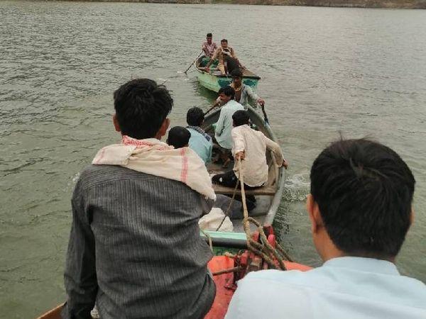नाव में बैठकर नदी से बाहर आती वैक्सीनेशन टीम।
