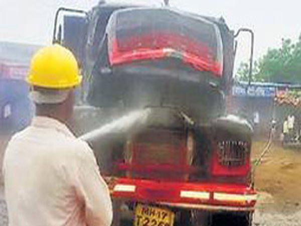 वाळूच्या ट्रकची आग विझवताना अग्निशामक दलाचा कर्मचारी. - Divya Marathi