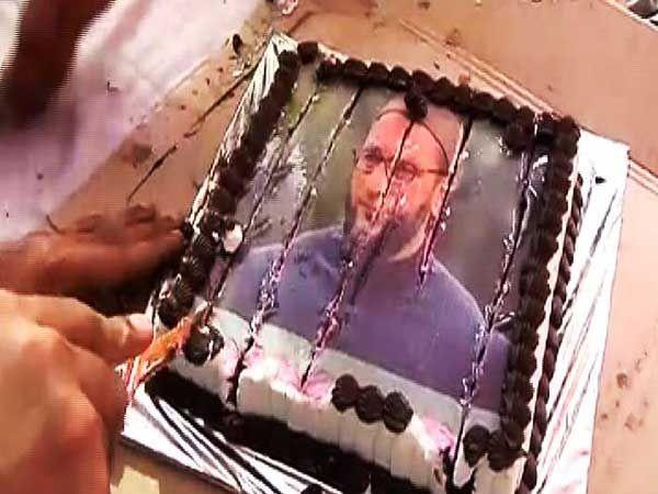 एमआयएयचे नेते व खासदार असदुद्दीन ओवेसी यांचा चेहरा असलेला केक कापताना राज ठाकरे... - Divya Marathi