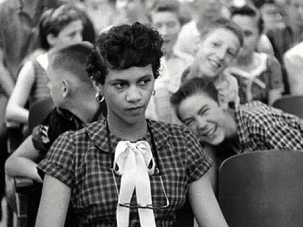 1957 - अमेरिकतील एका कृष्णवर्षीय तरुणीच्या शाळेतील पहिल्या दिवसाचा हा फोटो आहे. चार्लोट येथील हॅरी हार्डींग हायस्कूलमध्ये गोरे विद्यार्थी तिला चिडवत असल्याचे फोटोतही स्पष्ट दिसते. - Divya Marathi