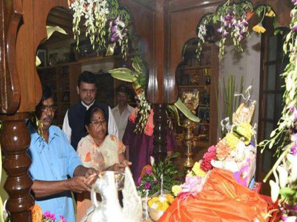 वर्षावरील गणेशाची पूजा करताना हेवाळेकर दांपत्य. - Divya Marathi