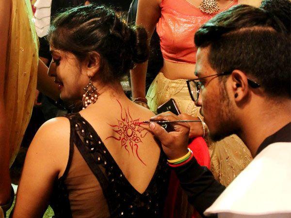 पाठीवर टॅटू गोंदवून घेतना तरुणी - Divya Marathi