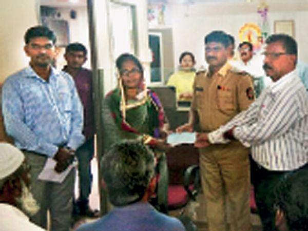 दोन लाखांचा धनादेश पोलिस निरीक्षक मुकुंद अघाव यांच्या हस्ते उषा जाधव यांना देण्यात आला. - Divya Marathi