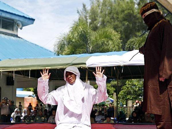 इंडोनेशियातील बंदा अचे येथे मशिदीबाहेर तरूणीला कोडे मारताना... - Divya Marathi