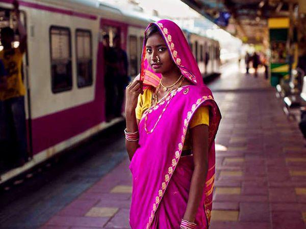 मुंबईच्या एका रेल्वे स्थानकावर ट्रेनची वाट पाहणारी महिला. - Divya Marathi