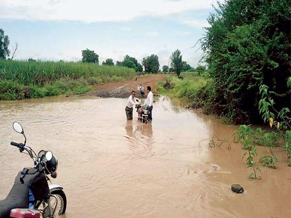 गेवराई तालुक्यातील आगरनांदूरयेथील रस्त्यावर नदीचे पाणी आल्याने शिक्षकांना पुराच्या पाण्यातून असा मार्ग काढावालागला. - Divya Marathi