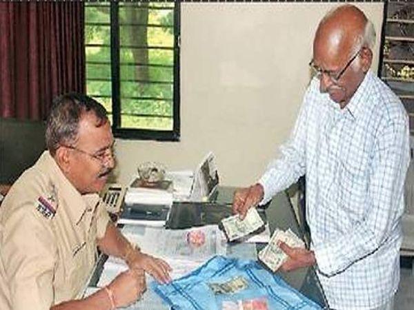 पोलिस निरीक्षक सुनील गायकवाड यांच्यासमोर पैसे मोजून घेताना दयानंद बिरहारी. - Divya Marathi