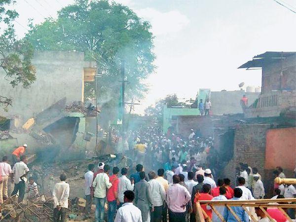 आष्टीतील दारूगल्ली भागात शुक्रवारी फटाका गोदामाला आग लागल्यानंतर सिलिंडरच्या स्फोटाने स्लॅबही कोसळला. स्लॅबखाली दबलेल्यांना बाहेर काढण्यासाठी नागरिकांनी गर्दी केली. - Divya Marathi