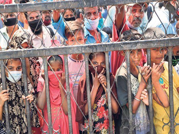 मुंबईच्या झोपडपट्टीतील मुलांसह सर्व लोक अन्नवाटपास येणाऱ्याची वाट पाहताहेत. - Divya Marathi