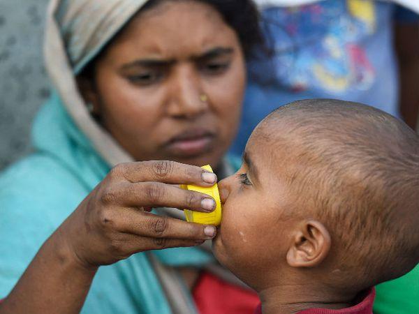 हे चित्र दिल्लीचे आहे. हे मजूर कुटुंब उत्तर प्रदेशातील गाजीपूर येथे पायी जात आहे. उन्हात एक आई आपल्या मुलाला पाणी पाजताना - Divya Marathi