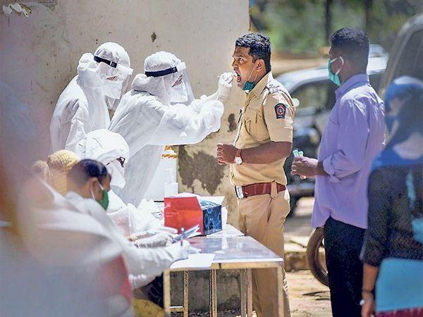 मुंबईतील धारावी येथील शिबिरात तपासणीसाठी दाखल झालेला पोलिस कर्मचारी - Divya Marathi