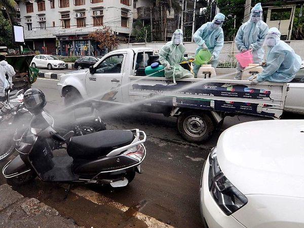 हे चित्र गुवाहाटीचे आहे, जेथे महापालिकेचे कर्मचारी रस्त्यावर जंतुनाशक औषध फवारत आहेत. - Divya Marathi