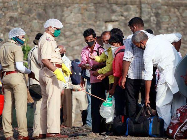 बस पकडण्यासाठी रांगेत उभ्या असलेल्या प्रवासी मजुरांना सोशल डिस्टन्स ठेवण्यास समजुन सांगताना पोलिस कर्मचारी - Divya Marathi