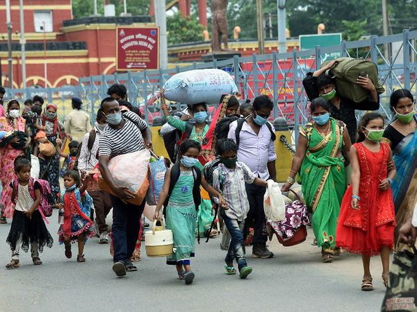 हा फोटो पाटण्यातील आहे. वेगवेगळ्या राज्यातील स्थलांतरित कामगार बसमध्ये जाण्यासाठी पायी जाताना - Divya Marathi